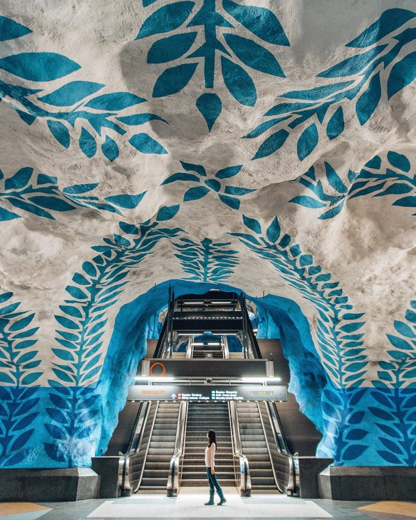 a girl standing inside an artsy subway station in stockholm sweden