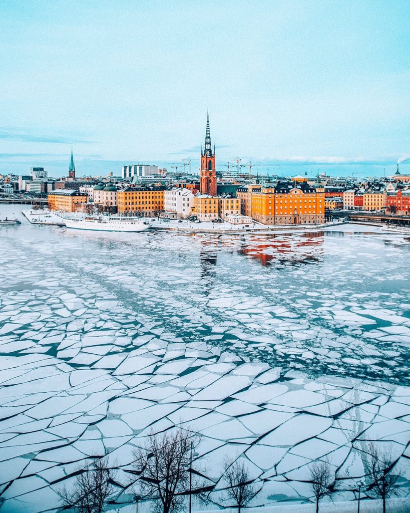 the view of stockholm sweden with a frozen lake in front of its old town