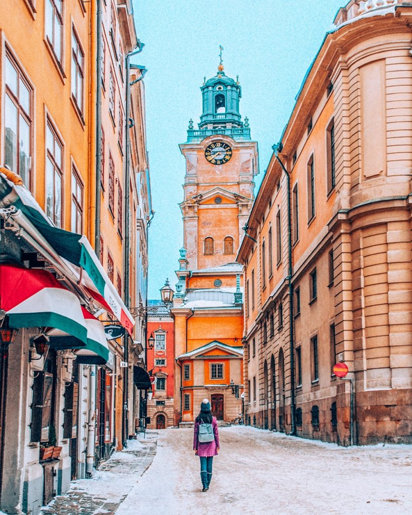 a girl walking in the colorful old town of stockholm sweden