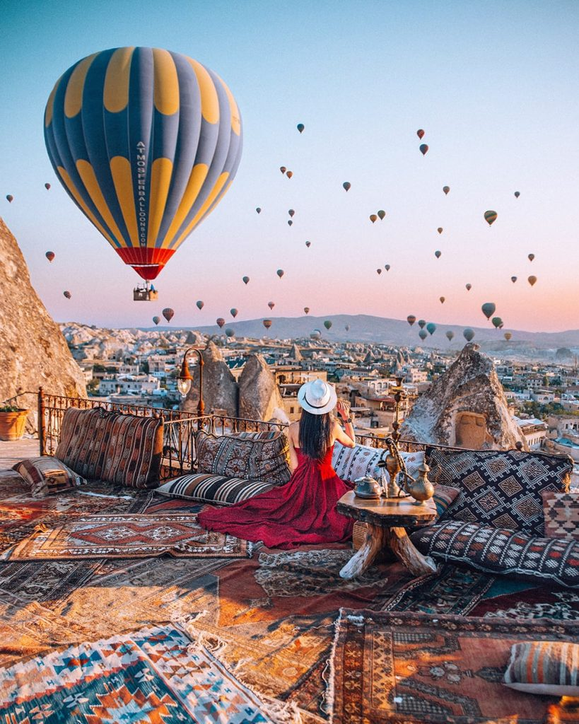 girl watching hot air balloons take off during sunrise in capadoccia turkey
