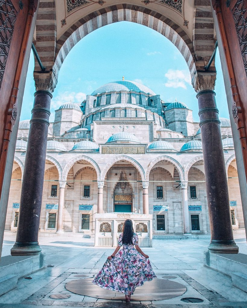 girl walking into suleymaniye mosque in istanbul turkey