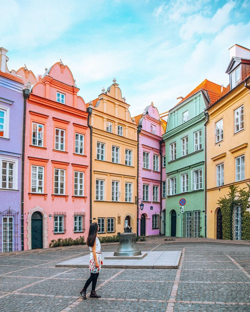 girl standing in front of colorful buildings in the old town of warsaw poland