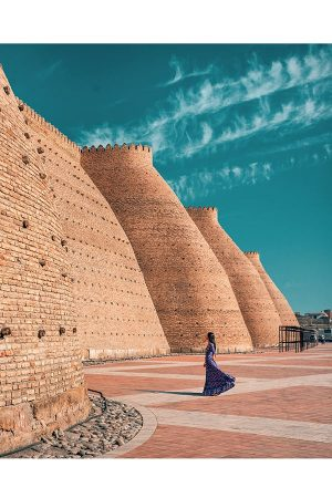 a girl standing in front of the ark of bukhara in uzbekistan