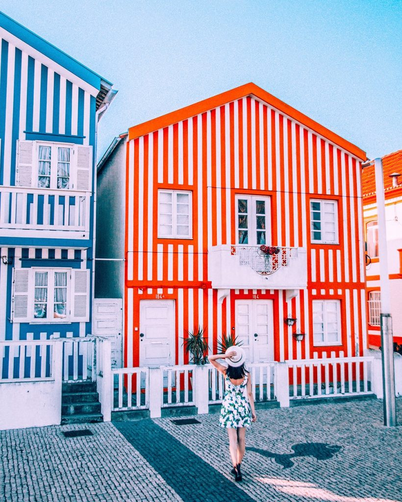 a girl walking towards a colorful striped house in aveiro portugal