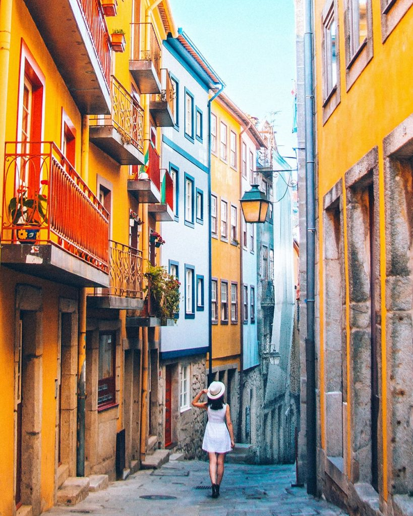 a girl walking amongst yellow buildings in porto portugal