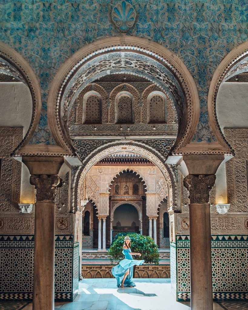 a girl standing in the royal alcazar of seville spain
