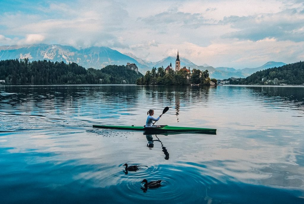 a woman kayaking in lake bled in slovenia