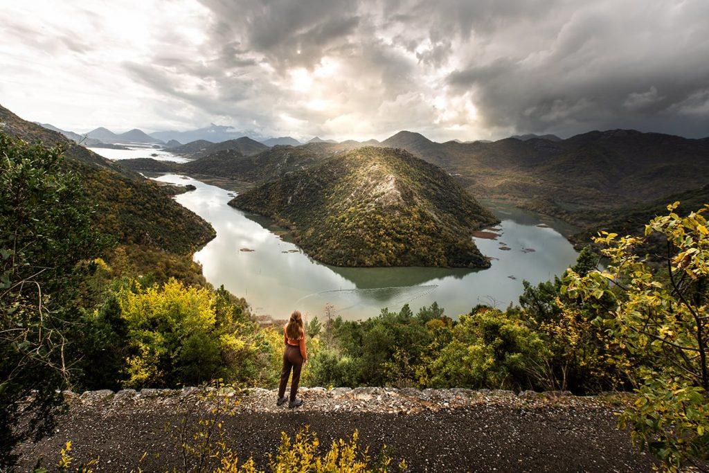a girl standing in front of lake skadar in montenegro