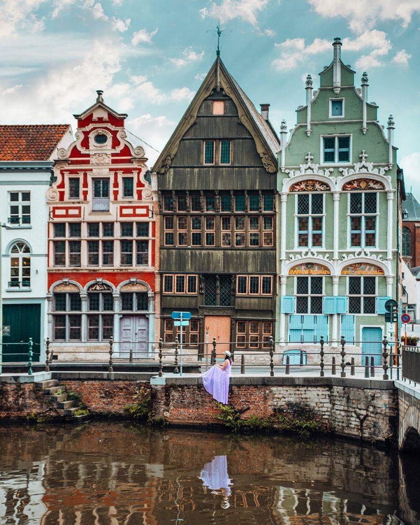 girl sitting in front of colorful buildings in mechelen belgium