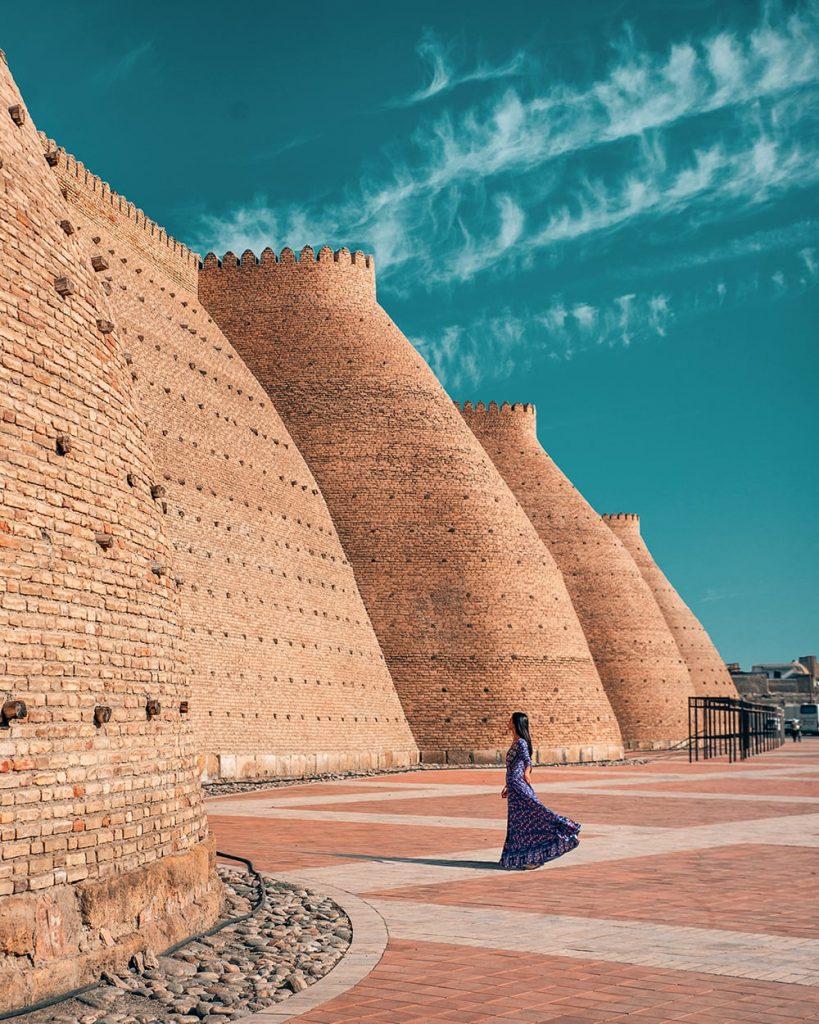 girl standing in front of the ark of bukhara in uzbekistan