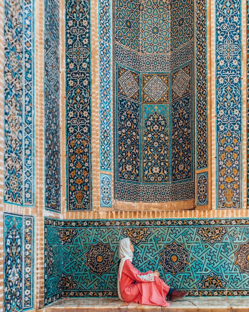 A Girl Sitting in Front of the Blue Tilework of Jameh Mosque in Yazd, Iran