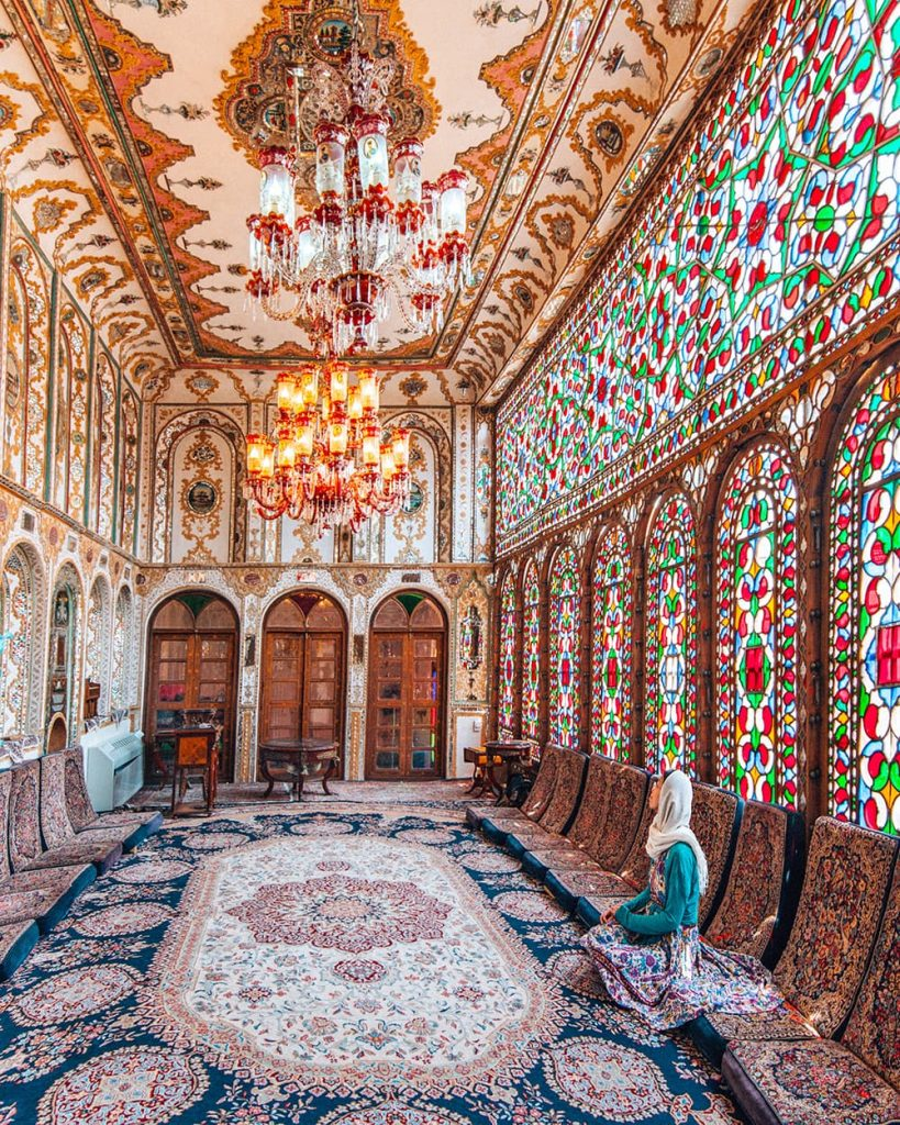 A Girl Sitting Next to the Stained Glass Windows of Mollabashi House in Isfahan, Iran