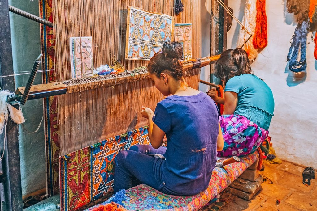 Locals Weaving A Silk Rug in a Handicrafts Workshop in Khiva Uzbekistan