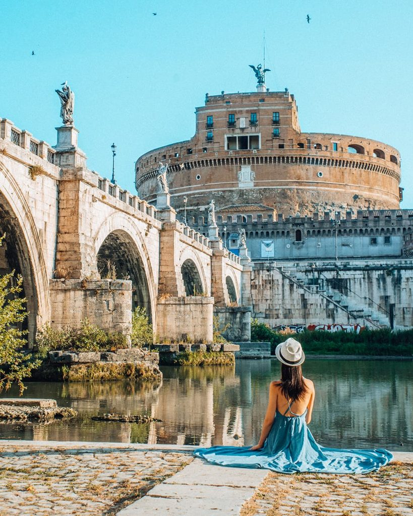 A Girl Sitting on the Riverbank of Tiber River With a View of Castel Sant'Angelo in Front of Her