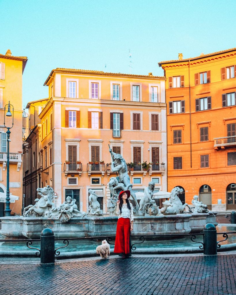 A Girl Standing in Front of a Fountain in Piazza Navona In the Morning in Rome, Italy
