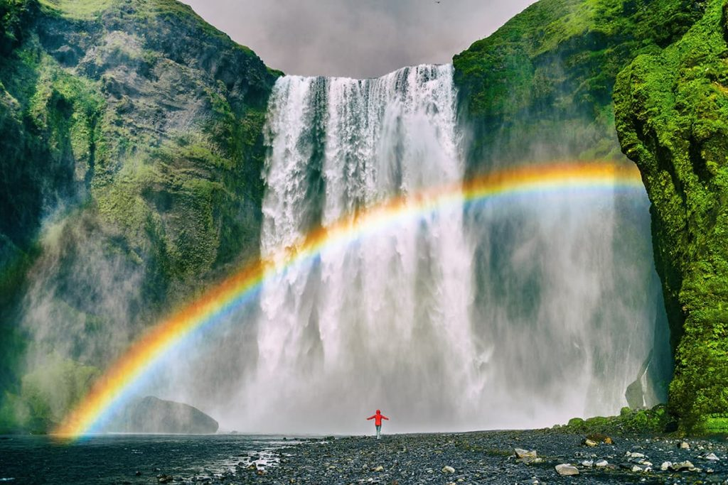 A Waterfall in Iceland With a Rainbow in the Sky