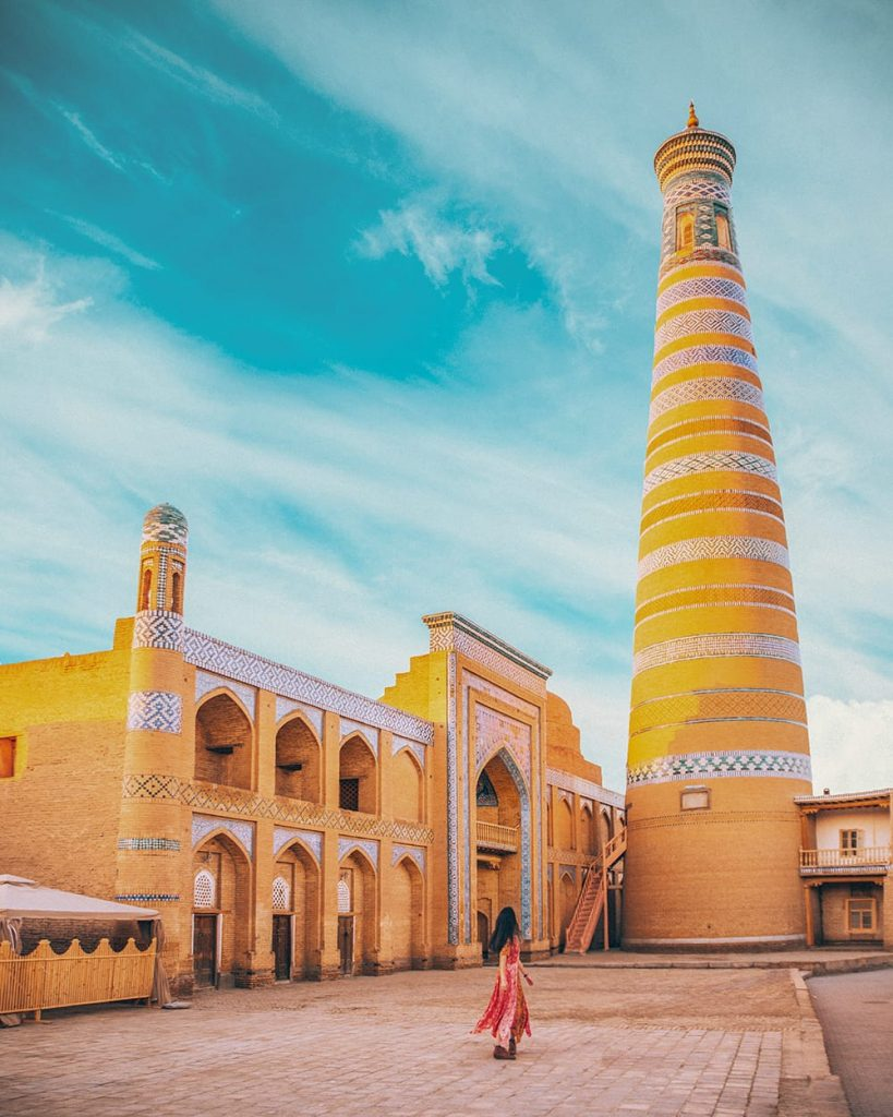 girl standing next to islom hoja minaret in khiva uzbekistan