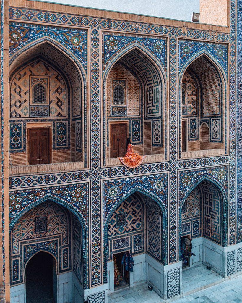 girl sitting on second floor of madrasah tile work in registan square