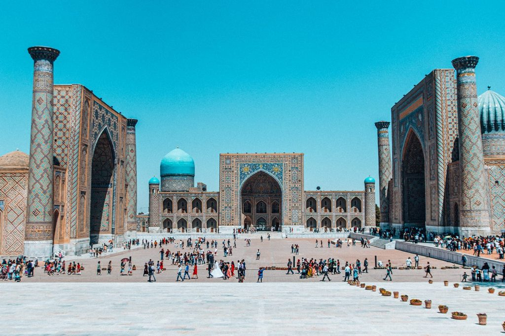 the three madrasahs in registan square filled with tourists in uzbekistan